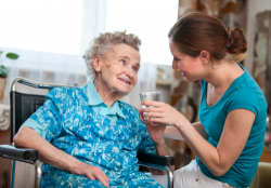 caregiver giving medication to an elderly woman in wheelchairs